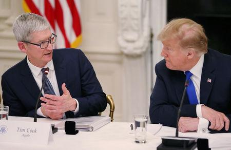 Apple CEO Tim Cook talks with U.S. President Donald Trump as they participate in an American Workforce Policy Advisory Board meeting in the White House State Dining Room in Washington, U.S., March 6, 2019. REUTERS/Leah Millis