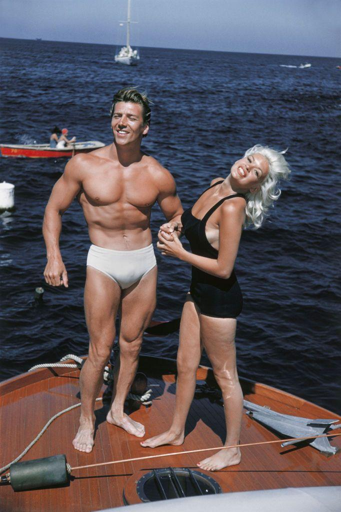 <p>Mickey Hargitay shows off his figure while posing with his wife, 1950s sex symbol Jayne Mansfield, on a boat in Catalina, California. Hargitay was a bodybuilder and won Mr. Universe in 1955. </p>