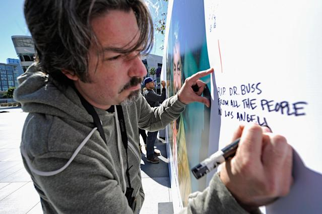 LOS ANGELES, CA - FEBRUARY 20: Lakers fan Mike Delahaut writes a personal message on the Dr. Buss Memorial Banners in the Nokia Plaza at L.A. Live, directly across the street from Staples Center on February 20, 2013 in Los Angeles, California. The Lakers will hold a memorial service to celebrate the life of longtime owner Jerry Buss at the Nokia Theater on Thursday, for invited guests only. Dr. Buss died at the age of 80 on Monday following an 18-month battle with cancer. (Photo by Kevork Djansezian/Getty Images)