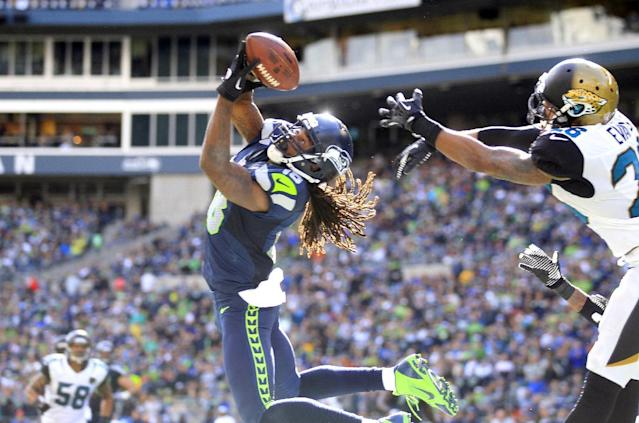 Seattle Seahawks' Sidney Rice, front left, snags the ball in the end zone for a touchdown in front of Jacksonville Jaguars' Josh Evans in the second half of an NFL football game on Sunday, Sept. 22, 2013, in Seattle. (AP Photo/Stephen Brashear)