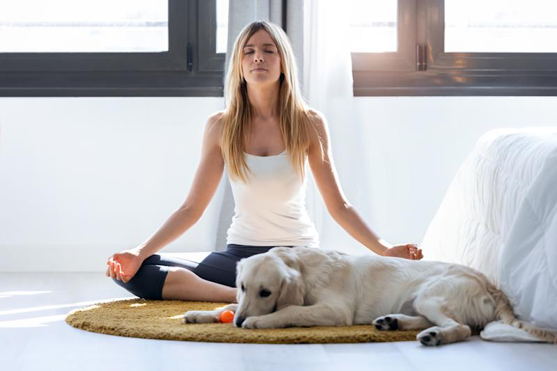 Shot of pretty young woman doing yoga while her dog lying on the floor at home.