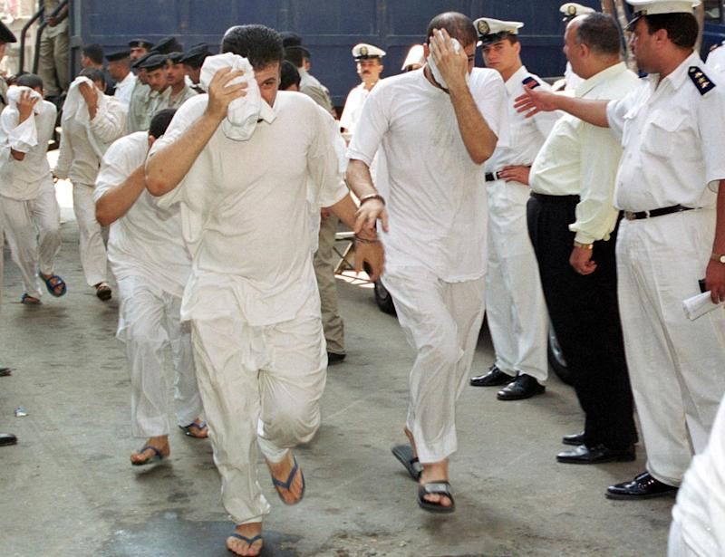 Egyptian men, accused of having gay sex, cover their faces as they walk into a Cairo court 18 July 2001
