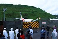 People gather outside a gate near the wreckage of an Air India Express jet at Calicut International Airport in Karipur, Kerala, on August 8, 2020. - Fierce rain and winds lashed a plane carrying 190 people before it crash-landed and tore in two at an airport in southern India, killing at least 18 people and injuring scores more, officials said on August 8. (Photo by Arunchandra BOSE / AFP) (Photo by ARUNCHANDRA BOSE/AFP via Getty Images)