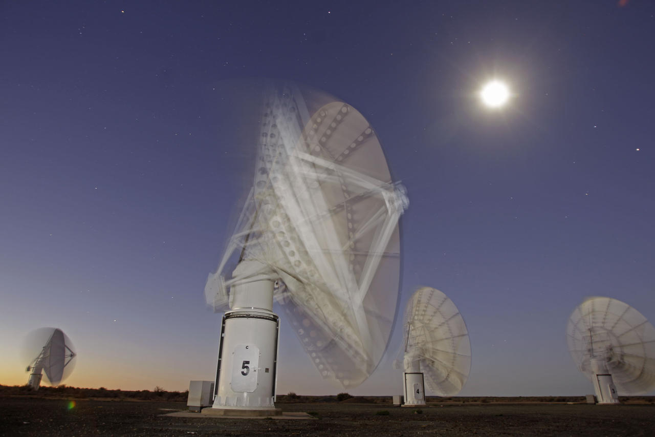 In this time exposure photo taken Monday, April 2, 2012, the moon and stars are seen above telescope dishes near the Karoo town of Carnarvon, South Africa, which is announced Friday May 25, 2012, as the site of the proposed Square Kilometre Array (SKA) radio telescope project. A giant radio telescope made up of some 3,000 separate 15-meter (49-foot) diameter dishes and intended to help scientists answer fundamental questions about the make-up of the universe will be built and based in both Australia and South Africa, the international consortium overseeing the project announced Friday. (AP Photo/Schalk van Zuydam) EDS NOTE: TIME EXPOSURE CAUSING BLUR AS TELESCOPE DISHES MOVE