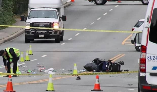 A loaded cart surrounded by cans and other recyclables is seen as authorities investigate a fatal pedestrian collision that left a man dead at the scene on the 13400 block of 96th Avenue in Surrey, B.C. on Sept. 4, 2021.  (Shane MacKichan - image credit)