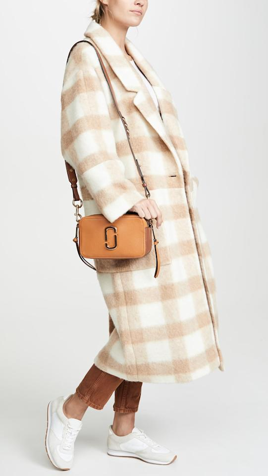 "<p>Go hands-free with this <a href=""https://www.popsugar.com/buy/Marc-Jacobs-Softshot-21-Bag-489593?p_name=Marc%20Jacobs%20The%20Softshot%2021%20Bag&retailer=shopbop.com&pid=489593&price=350&evar1=fab%3Aus&evar9=46601136&evar98=https%3A%2F%2Fwww.popsugar.com%2Ffashion%2Fphoto-gallery%2F46601136%2Fimage%2F46602229%2FMarc-Jacobs-Softshot-21-Bag&list1=shopping%2Cfall%20fashion%2Cbags%2Chandbags&prop13=api&pdata=1"" rel=""nofollow"" data-shoppable-link=""1"" target=""_blank"" class=""ga-track"" data-ga-category=""Related"" data-ga-label=""https://www.shopbop.com/softshot-bag-marc-jacobs/vp/v=1/1590126363.htm?folderID=13505&amp;fm=other-viewall&amp;os=false&amp;colorId=1196A"" data-ga-action=""In-Line Links"">Marc Jacobs The Softshot 21 Bag</a> ($350).</p>"