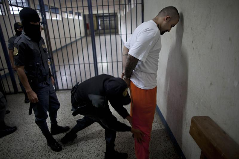 """In this Aug. 29, 2012 photo, the leader of the Guatemala branch of the M-18 gang, Aldo Dupie Ochoa Mejia, alias """"El Lobo"""" or """"The Wolf,"""" is frisked by prison guards inside the Frajines 1 prison in Guatemala City. Mejia says his gang is considering and willing to make a truce with their rival, the MS-13 gang, such as the one that appears to be holding in El Salvador. (AP Photo/Rodrigo Abd)"""
