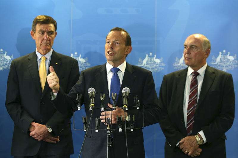 """Australian Prime Minister Tony Abbott, center, addresses the media with former Defense Force Chief Angus Houston, left, and Deputy Prime Minister Warren Truss at RAAF base Pearce on Monday, March 31, 2014, in Bullsbrook, near Perth, Australia. Abbott said the search for Malaysia Airlines Flight 370 is """"an extraordinarily difficult exercise"""" but that it will go on as long as possible. Abbott said Monday that although no debris has been found in the southern Indian Ocean that can be linked to the plane missing for more than three weeks, the searchers are """"well, well short"""" of any point where they would scale the hunt back. (AP Photo/Paul Kane, Pool)"""