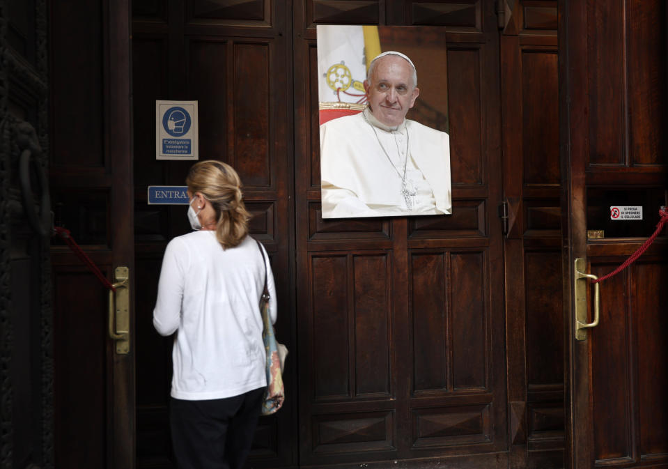 A woman passes past a portrait of Pope Francis as she enters the Argentine church of Santa Maria Addolorata (Our Lady of Sorrows) in Rome, Sunday, July 4, 2021. Pope Francis was hospitalized in Rome on Sunday afternoon for scheduled surgery on his large intestine, the Vatican said. The news came just three hours after Francis had cheerfully greeted the public in St. Peter's Square and told them he will go to Hungary and Slovakia in September. (AP Photo/Riccardo De Luca)