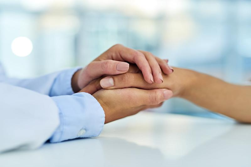 Closeup shot of a doctor holding a patient's hand in comfort