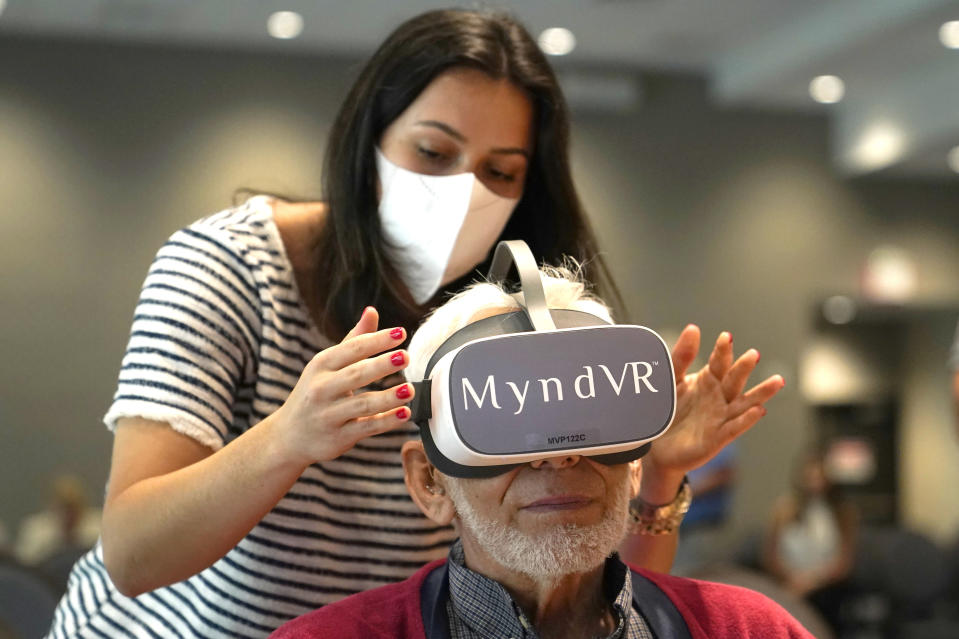Gloria Gantes, left, adjusts the goggles of resident John Dalsimer as he participates in a virtual reality study at John Knox Village, Tuesday, June 1, 2021, in Pompano Beach, Fla. The senior community is in partnership with Stanford University's Virtual Human Interaction Lab on a study to see how older adults respond to virtual reality and whether it can improve their sense of wellbeing. (AP Photo/Lynne Sladky)