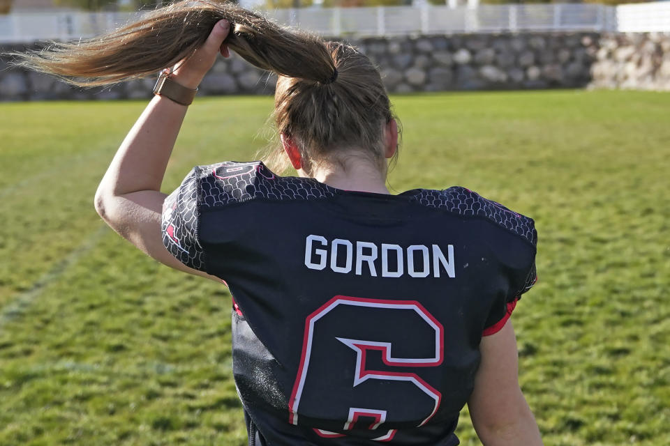 Sam Gordon adjusts her ponytail as she walks across a field, Oct. 20, 2020, in Herriman, Utah. Gordon was the only girl in a tackle football league when she started playing the game at age 9. Now, Gordon hopes she can give girls a chance to play on female-only high school teams through a lawsuit. (AP Photo/Rick Bowmer)