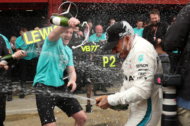 Formula One F1 - Spanish Grand Prix - Circuit de Barcelona-Catalunya, Barcelona, Spain - May 13, 2018 Mercedes' Lewis Hamilton is sprayed with champagne by a member of his team as they celebrate after taking first and second place in the race REUTERS/Albert Gea