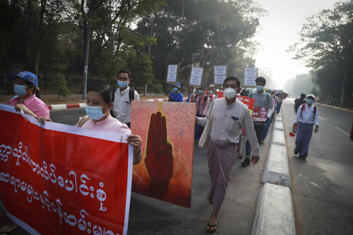 University teachers hold posters during a street march in Yangon, Myanmar, Friday, Feb. 26, 2021. Social media giant Facebook announced Thursday it was banning all accounts linked to Myanmar's military as well as ads from military-controlled companies in the wake of the army's seizure of power on Feb. 1. (AP Photo)