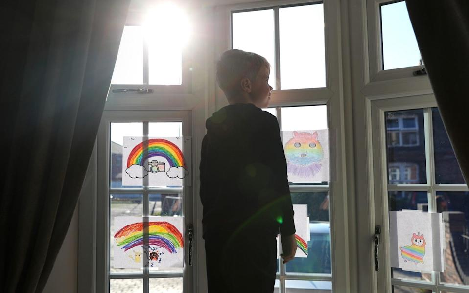 A young boy looks out of a window of his home after drawing a rainbow picture in Stockport, England - Getty