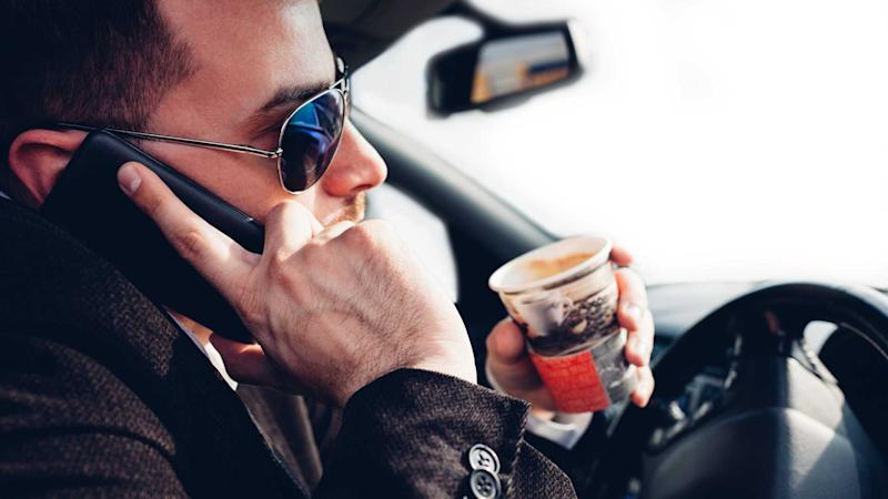 Distracted man drinking coffee and using mobile phone while driving car