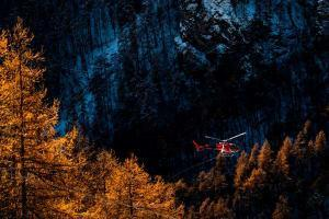 A helicopter flies over an Italian forest.