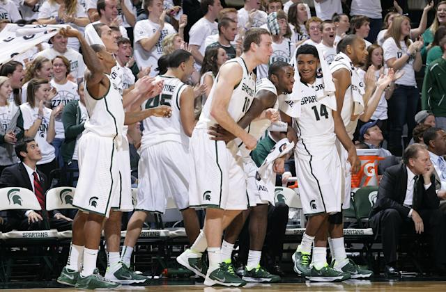 Michigan State's Keith Appling, left, Gavin Schilling, left rear, Denzel Valentine (45), Matt Costello (10), Branden Dawson, Gary Harris (14) and Adreian Payne celebrate on the bench during the first half of an NCAA college basketball exhibition game against Grand Valley State, Tuesday, Oct. 29, 2013, in East Lansing, Mich. Seated at right is coach Tom Izzo. Michigan State won 101-52. (AP Photo/Al Goldis)