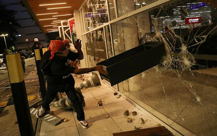 A demonstrator damages a storefront - REUTERS