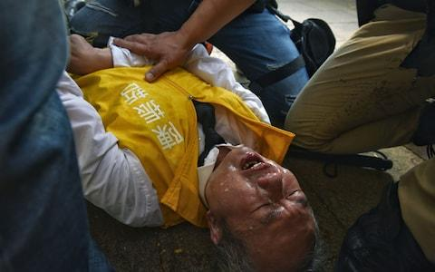 <span>Chan, a candidate for district council elections, lies on the floor after being pepper-sprayed</span> <span>Credit: MIGUEL CANDELA/EPA </span>