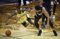 Oregon forward Eugene Omoruyi (2) and Colorado forward Evan Battey (21) reach for the ball during the first half of an NCAA college basketball game Thursday, Feb. 18, 2021, in Eugene, Ore. (AP Photo/Andy Nelson)