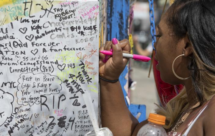 "Diana Rutledge of Dayton, Ohio, writes a message on a mural honoring Los Angeles Lakers legend Kobe Bryant and his daughter Gianna, located in the 1200 block of South La Brea Avenue in Los Angeles. <span class=""copyright"">(Mel Melcon / Los Angeles Times)</span>"