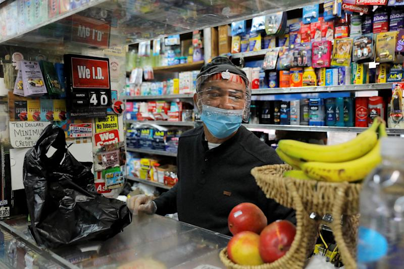 Bodega manager Rafael Perez wears a homemade face protector, fashioned from a water bottle, as he works in the Chinese Hispanic Grocery during the coronavirus disease (COVID-19) outbreak in the Lower East Side neighborhood of Manhattan, New York City, New York, U.S., April 2, 2020. REUTERS/Andrew Kelly