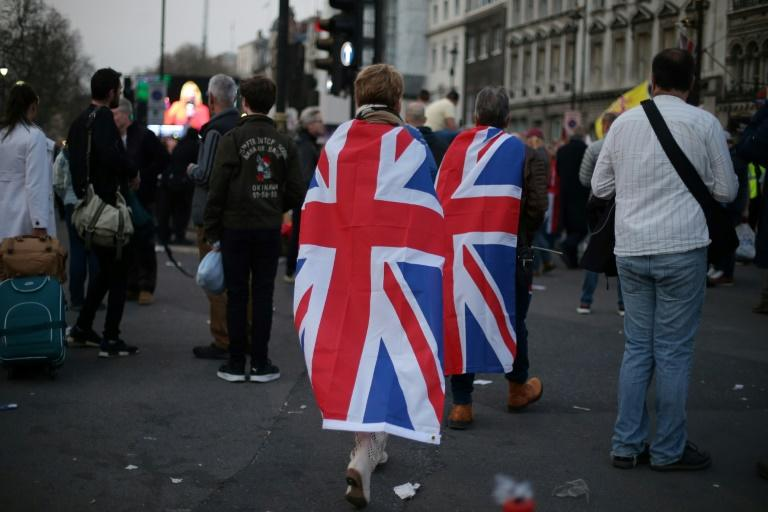 Pro-Brexit supporters draped in Union Flags leave at the end of a rally outside the Houses of Parliament in central London after MPs voted down the government's Brexit deal for a third time