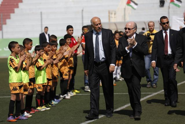 FIFA President Sepp Blatter (C) smiles as he visits a football academy named after him, near the West Bank city of Ramallah May 27, 2014. REUTERS/Mohamad Torokman (WEST BANK - Tags: POLITICS SPORT)