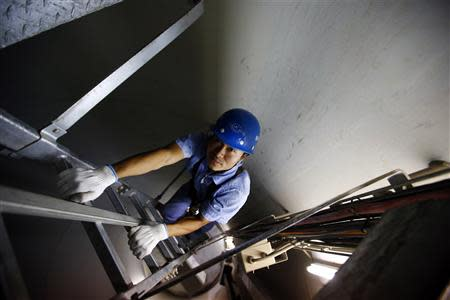 A worker inspects the interior of a wind turbine used to generate electricity, at a wind farm in Guazhou, 950km (590 miles) northwest of Lanzhou, Gansu Province September 15, 2013. REUTERS/Carlos Barria
