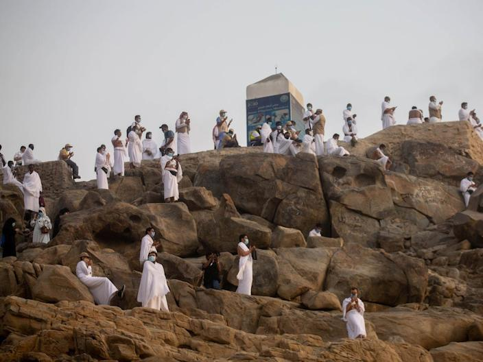 Muslim pilgrims wear protective face masks, as they pray on Mount Mercy on the plains of Arafat during the annual Hajj pilgrimage, on July 30, 2020.