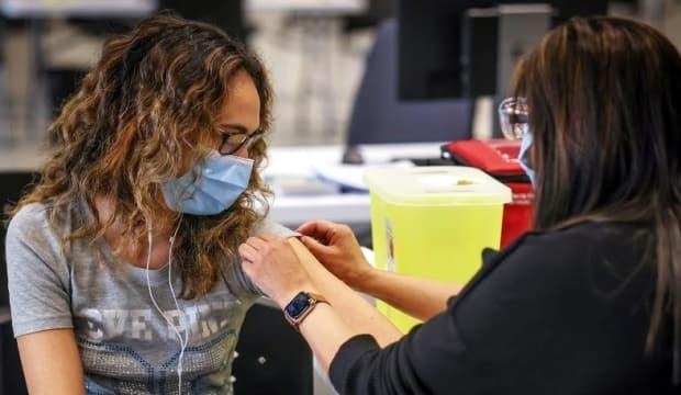 Nicole Fuerderer, 23, receives a COVID-19 vaccine from public health nurse Nashrin Valani at the Telus Convention Centre mass-vaccination clinic in Calgary on April 19, 2021. A similar clinic just for northeast and east Calgary residents who need their first doses of a vaccine happens this weekend. (Leah Hennel/AHS - image credit)
