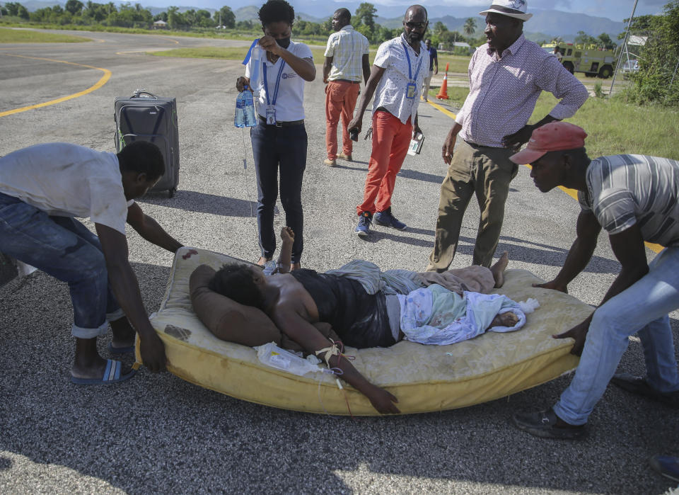 FILE - In this Aug. 14, 2021 file photo, a woman injured in a 7.2 magnitude earthquake, is transferred on a mattress to a plane to be flown to Port-au-Prince, in Les Cayes, Haiti, Saturday, Aug. 14, 2021. Haitians continue to show up at hospitals seeking care for injuries after an earthquake battered their country. (AP Photo/Joseph Odelyn, File)