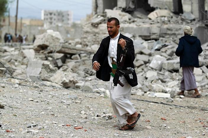A Yemeni flees as an air-strike by the Saudi-led coalition re-targets a house, said to belong to a Huthi leader in the capital Sanaa on May 29, 2015 (AFP Photo/Mohammed Huwais)