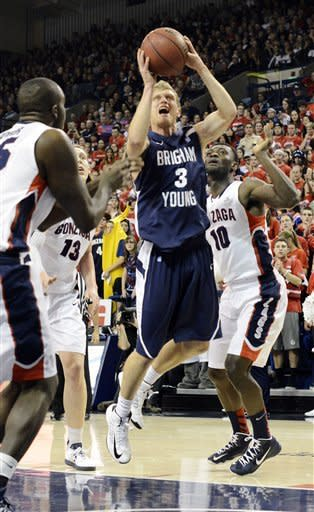Bringham Youngs's Tyler Haws (3) shoots as Gonzaga's Guy Landry Edi (10) and Kelly Olynyk (13) defend in the first half of an NCAA college basketball game, Thursday, Jan. 24, 2013, in Spokane, Wash. (AP Photo/Jed Conklin)