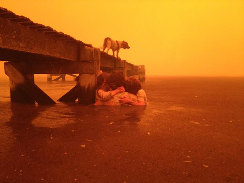 In this Jan. 4, 2013, photo provided by the Holmes family,  Tammy Holmes and her grandchildren take refuge under a jetty as a wildfire rages nearby in the Tasmanian town of Dunalley, east of the state capital of Hobart, Australia. The family credits God with their survival from the fire that destroyed around 90 homes in Dunalley. Record temperatures across southern Australia cooled Wednesday, Jan. 9, 2013, reducing the danger from scores of raging wildfires but likely bringing only a brief reprieve from the summer's extreme heat and fire risk. (AP Photo/Holmes Family, Tim Holmes) EDITORIAL USE ONLY