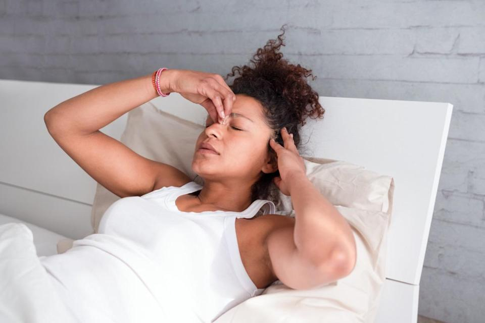 woman feeling sick and uncomfortable in bed