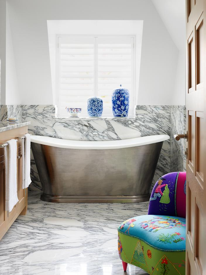 """<div class=""""caption""""> The master bath features a <a href=""""https://www.cphart.co.uk/"""" rel=""""nofollow noopener"""" target=""""_blank"""" data-ylk=""""slk:C.P. Hart"""" class=""""link rapid-noclick-resp"""">C.P. Hart</a> tub. Embroidered chair by Minnie. </div> <cite class=""""credit"""">Simon Upton </cite>"""