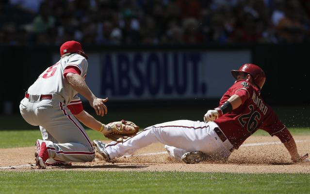 Arizona Diamondbacks' Miguel Montero (26) slides safely into third base as Philadelphia Phillies' Cody Asche, left, applies a late tag during the fourth inning of a baseball game on Sunday, April 27, 2014, in Phoenix. (AP Photo/Ross D. Franklin)
