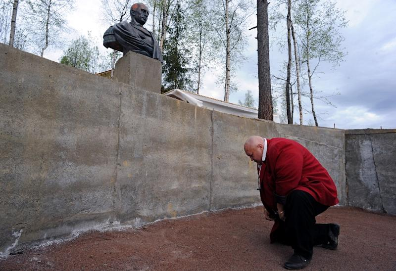 A man bows in front of a sculpture of Russian President Vladimir Putin in the village of Agalatovo, about 30 km from Saint Petersburg, on May 16, 2015 (AFP Photo/Olga Maltseva)