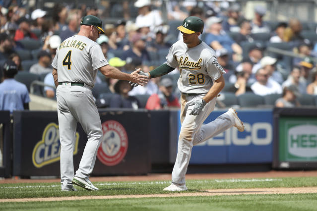 Oakland Athletics' Matt Olson (28) celebrates hitting a two-run home run with Athletics third base coach Matt Williams (4) during the fourth inning of a baseball game against the New York Yankees, Saturday, Aug. 31, 2019, in New York. (AP Photo/Mary Altaffer)