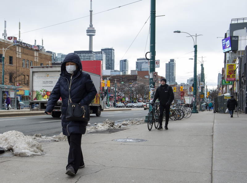 A pedestrian wears a protective mask in Toronto on Monday, Jan. 27, 2020. Canada's first presumptive case of the novel coronavirus has been officially confirmed, Ontario health officials said Monday as they announced the patient's wife has also contracted the illness. (Frank Gunn/The Canadian Press via AP)
