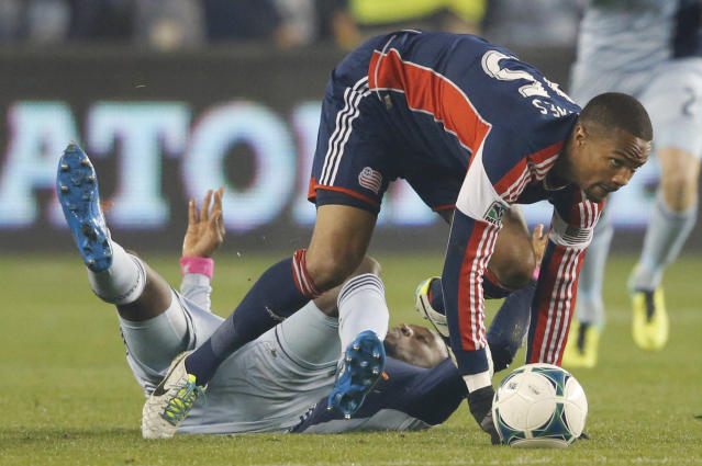 New England Revolution defender Darrius Barnes (25) gets away from Sporting Kansas City forward C.J. Sapong, back, during the first half of an MLS playoff soccer match in Kansas City, Kan., Wednesday, Nov. 6, 2013. (AP Photo/Orlin Wagner)