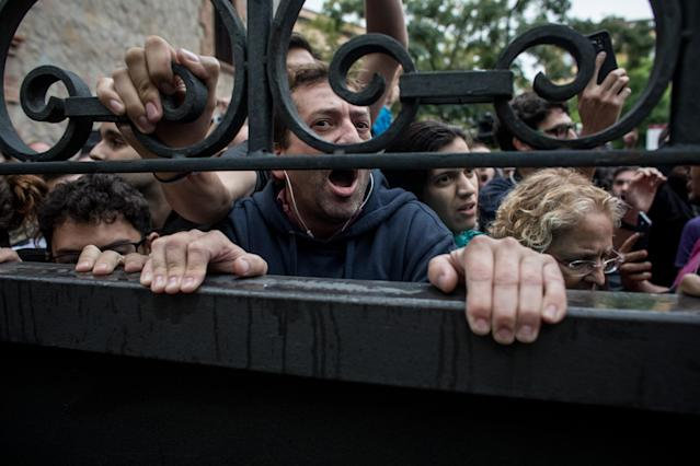 <p>Pro-referendum supporters lock a gate to a polling station as members of the Spanish National Police arrived to control the area during voting at the Escola Industrial of Barcelona school polling station on Oct. 1, 2017 in Barcelona, Spain. (Photo: Chris McGrath/Getty Images) </p>