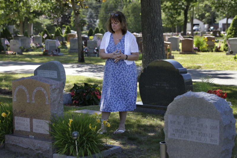 FILE - In this Tuesday, June 19, 2018 file photo, Cheryl Juaire, of Marlborough, Mass., stands at her son's grave, in Chelmsford, Mass. Victims of opioid addiction weren't in the room when big decisions were hammered out in OxyContin maker Purdue Pharma's proposal to settle claims over its role in the U.S. opioid crisis. Cheryl Juaire lost her 23-year-old son to a heroin overdose after he became addicted to prescription painkillers. (AP Photo/Steven Senne, File)