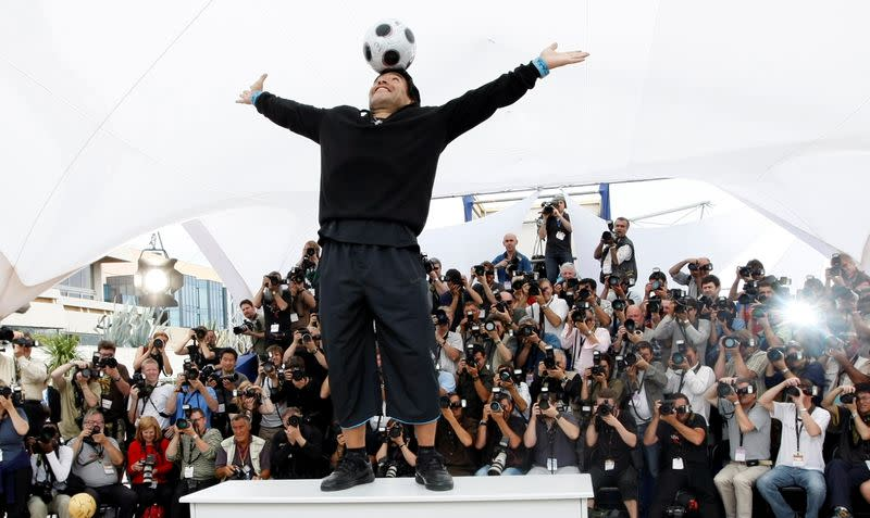 FILE PHOTO: Former soccer star Maradona balances a ball on his head during a photocall at the 61st Cannes Film Festival