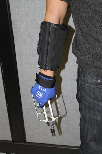 Demonstration of RoboGlove — spinoff technology from NASA's Robonaut program — providing assistance with a grasping task.