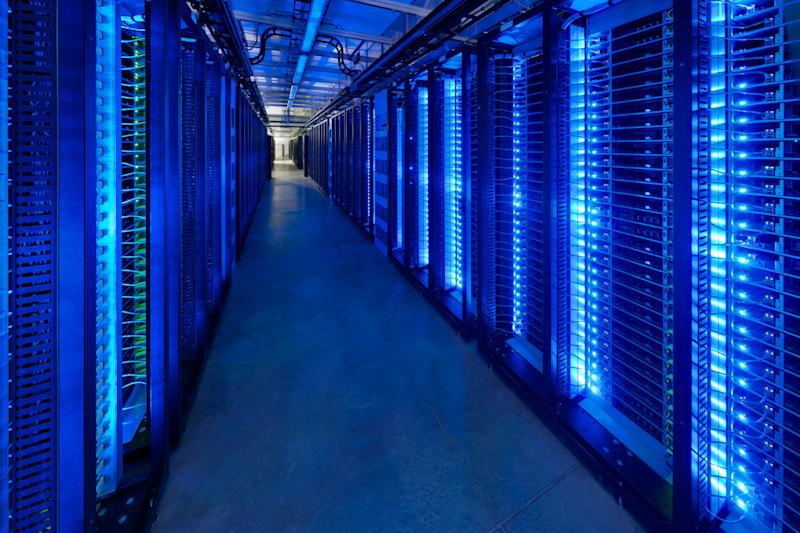 Dark data center room with blue glowing server lights.