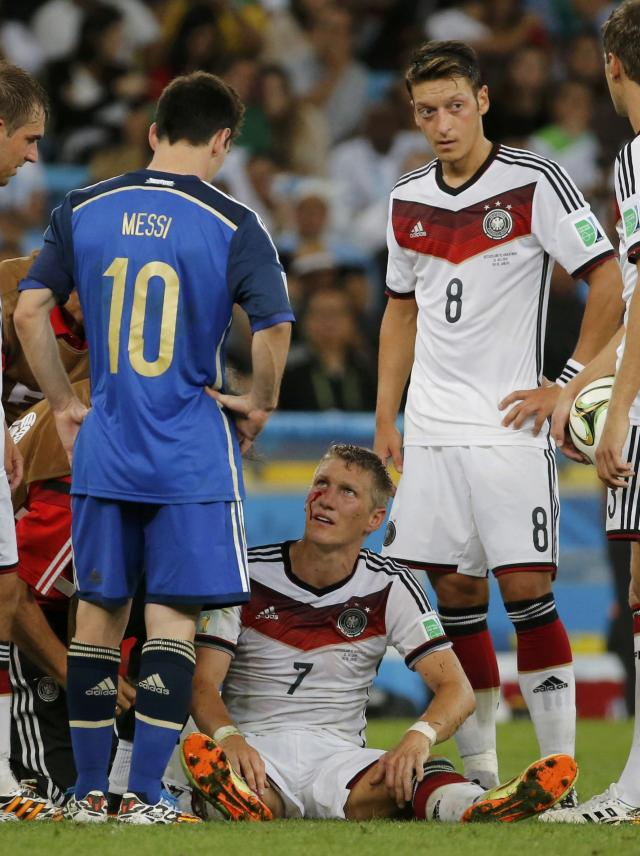 Germany's Bastian Schweinsteiger sits in the pitch injured after colliding with Argentina's Sergio Aguero during extra time in their 2014 World Cup final at the Maracana stadium in Rio de Janeiro July 13, 2014. REUTERS/Sergio Moraes (BRAZIL - Tags: SOCCER SPORT WORLD CUP)