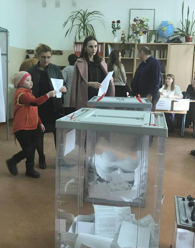A voter (R, front) walks with a ballot at a polling station number 217 during the presidential election in Ust-Djeguta, Russia March 18, 2018. The voter, asked by a Reuters reporter to explain why she was voting multiple times, ignored the question and walked away. Picture taken March 18, 2018. REUTERS/Tatiana Voronova